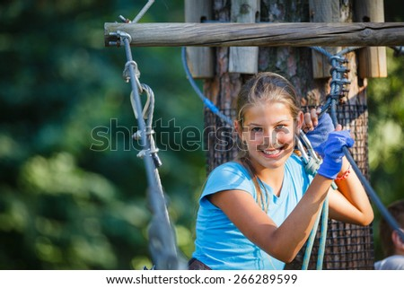 Portrait of happy school girl enjoying activity in a climbing adventure park on a summer day