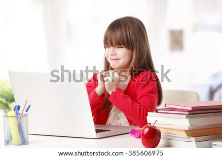 Portrait of happy school girl working on laptop while sitting at desk behind it.   - stock photo