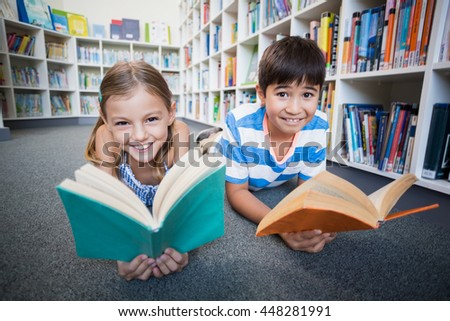 Portrait of happy school kids lying on floor and reading a book in library at school - stock photo