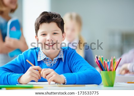 Portrait of happy schoolboy at workplace looking at camera with his classmates on background - stock photo