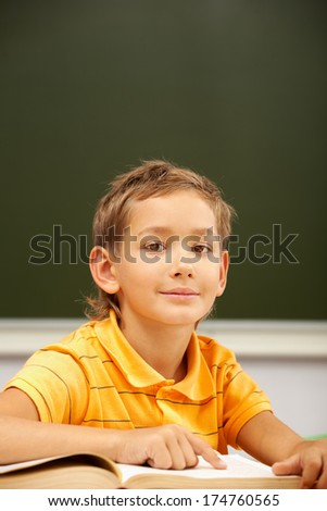 Portrait of happy schoolboy looking at camera during reading lesson - stock photo