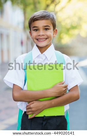 Portrait of happy schoolboy standing in campus with book at school - stock photo