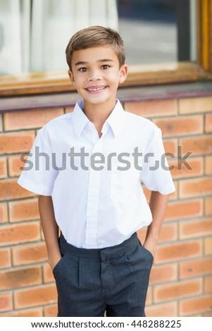 Portrait of happy schoolboy standing in corridor with hands in pocket at school - stock photo
