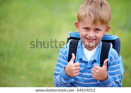 portrait of happy schoolboy with satchel on his back - stock photo