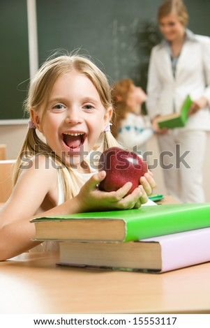 Portrait of happy schoolgirl and apple in her hands sitting at the table with books