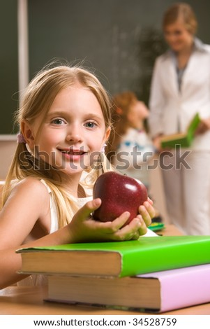 Portrait of happy schoolgirl and apple in her hands sitting at the table with books - stock photo