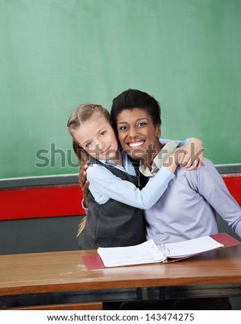 Portrait of happy schoolgirl hugging female professor at desk in classroom - stock photo
