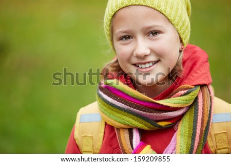 Portrait of happy schoolgirl looking at camera outside - stock photo