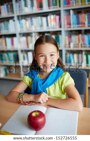 Portrait of happy schoolgirl sitting and looking at camera in library - stock photo