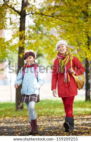 Portrait of happy schoolgirls in casual going home after school - stock photo