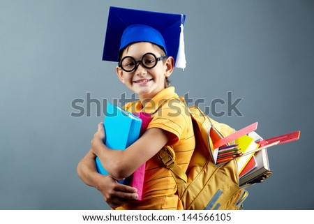 Portrait of happy schoolkid with backpack looking at camera - stock photo