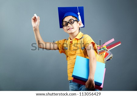 Portrait of happy schoolkid with chack, backpack and books - stock photo