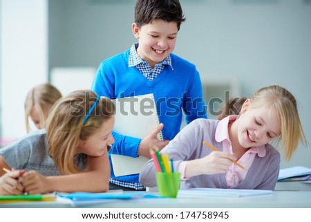 Portrait of happy schoolkids looking at girl picture and having fun - stock photo