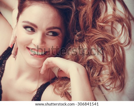 Portrait of happy seductive woman wearing lingerie in bed at home. Attractive sensual smiling young girl with long hair. Female underwear fashion. - stock photo