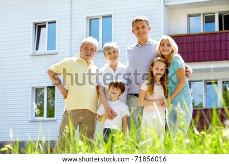 Portrait of happy senior and young couples standing outdoors with new cottage at background - stock photo