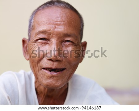 Portrait of happy senior asian man with dental problems laughing and looking at camera against yellow wall - stock photo