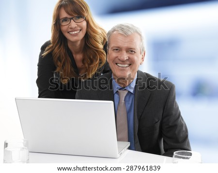 Portrait of happy senior businessman sitting behind the laptop while sales woman standing next to colleague and looking at camera. Teamwork at office.  - stock photo
