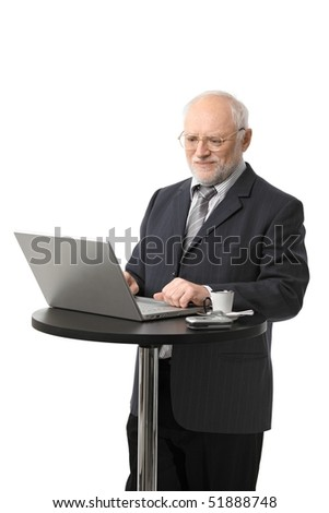 Portrait of happy senior businessman using laptop on coffee table, isolated on white.