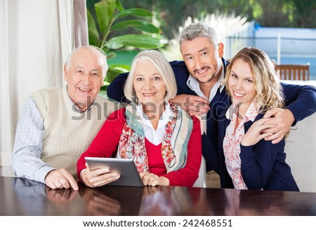 Portrait of happy senior couple and grandchildren with digital tablet in nursing home - stock photo