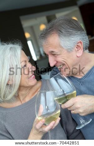 Portrait of happy senior couple cheering with wine - stock photo
