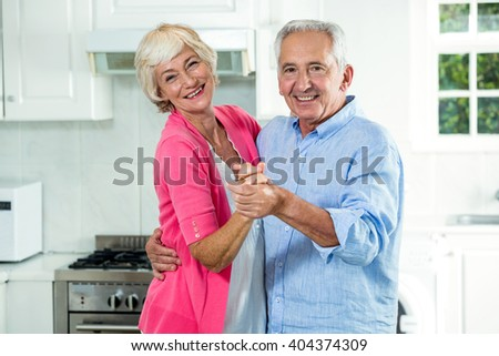 Portrait of happy senior couple dancing in kitchen - stock photo