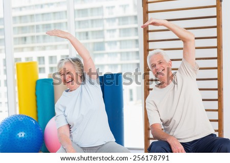 Portrait of happy senior couple doing stretching exercise in gym - stock photo