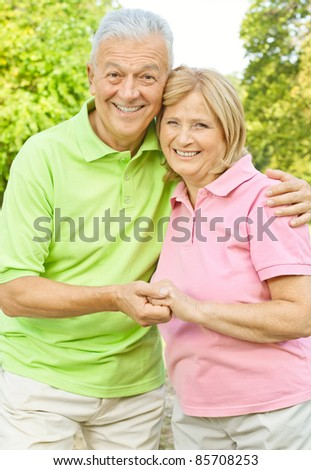 Portrait of happy senior couple holding hands outdoors. - stock photo