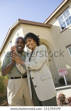 Portrait of happy senior couple holding key in front of new house - stock photo