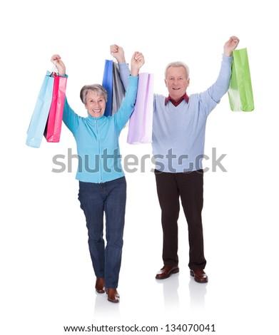 Portrait Of Happy Senior Couple Holding Shopping Bags - stock photo