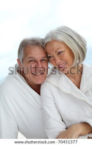 Portrait of happy senior couple in spa center - stock photo