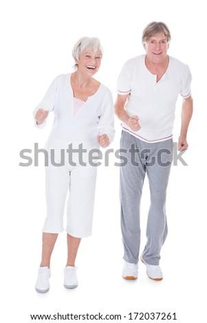 Portrait Of Happy Senior Couple Jogging On White Background - stock photo