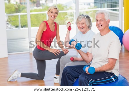 Portrait of happy senior couple lifting dumbbells by trainer in gym - stock photo