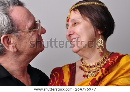 Portrait of happy senior couple looking at each other. Husband and wife wearing Indian clothing sari, tikka and necklace - stock photo
