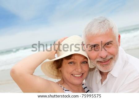 Portrait of happy senior couple on a sandy beach - stock photo