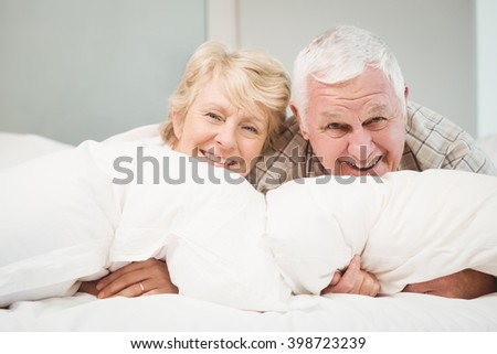 Portrait of happy senior couple resting on bed at home - stock photo