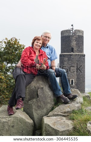 Portrait of happy senior couple resting on the rocks next to the ruins of Hazmburk castle in the Czech Republic. - stock photo
