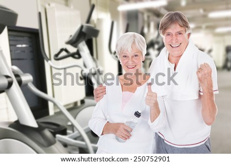 Portrait Of Happy Senior Couple Showing Thumb Up Gesture At Fitness Gym - stock photo