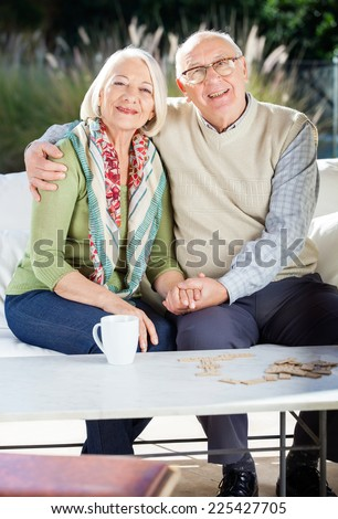 Portrait of happy senior couple sitting arm around on couch at nursing home porch - stock photo