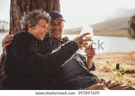 Portrait of happy senior couple sitting near a lake toasting with wine on camping. Woman and man drinking wine at campsite. - stock photo