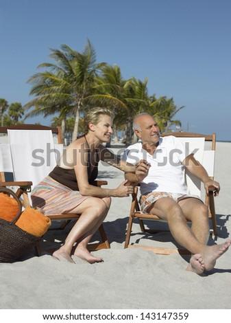 Portrait of happy senior couple sitting on deckchairs at sunny beach - stock photo