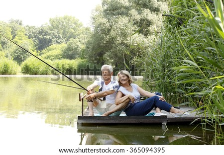 Portrait of happy senior couple sitting on pier at lakeshore while fishing together.