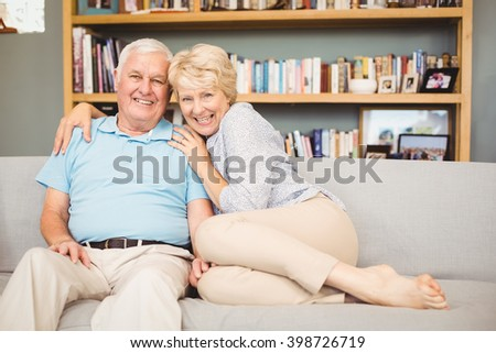 Portrait of happy senior couple sitting on sofa against bookshelf in living room - stock photo