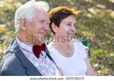 Portrait of happy senior couple sitting on the bench - stock photo
