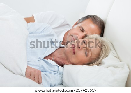 Portrait Of Happy Senior Couple Sleeping Together In Bed - stock photo