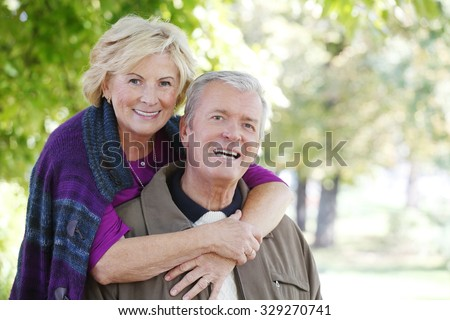 Portrait of happy senior couple  smiling to the camera while relaxing at outdoor and elderly woman hugging old man.  - stock photo