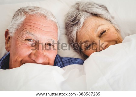 Portrait of happy senior couple smiling while lying on bed in bedroom - stock photo