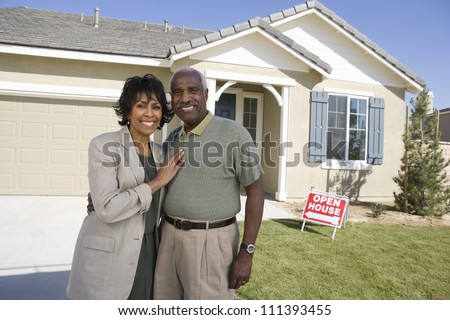 Portrait of happy senior couple standing in front of house - stock photo