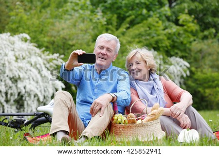 Portrait of happy senior couple taking selfies with smart phone while picnic and relaxing outdoor. - stock photo