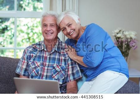 Portrait of happy senior couple using laptop at home - stock photo