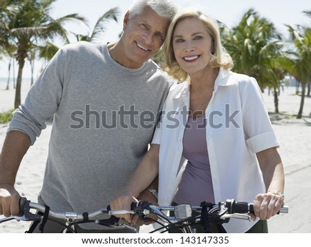 Portrait of happy senior couple with bicycles on tropical beach - stock photo